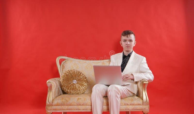 Portret młody nastoletni mężczyzna jest ubranym białego biurowego kostium i obsiadanie na złotej luksusowej kanapie na czerwonym  zdjęcia stock