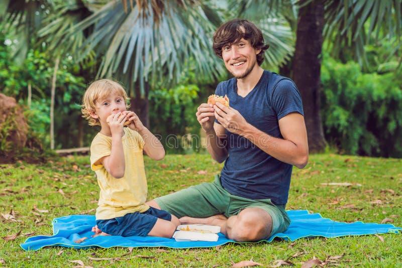 Portret młody ojciec i jego syn cieszy się hamburger w ono uśmiecha się i parku obraz royalty free