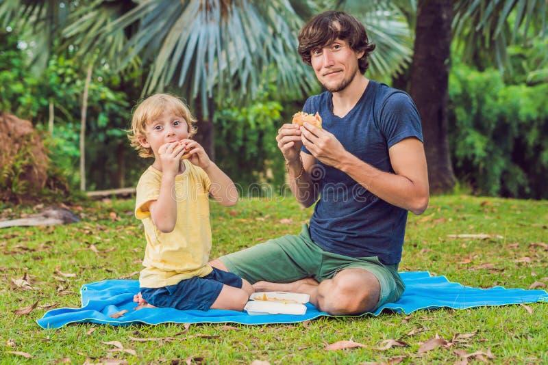 Portret młody ojciec i jego syn cieszy się hamburger w ono uśmiecha się i parku obraz stock