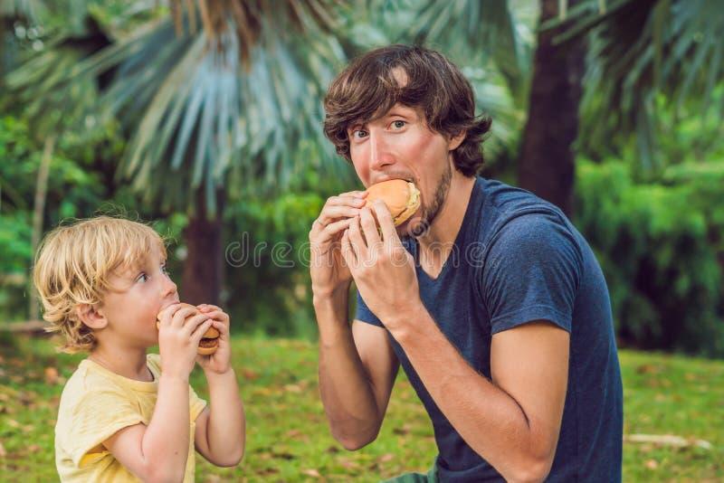 Portret młody ojciec i jego syn cieszy się hamburger w ono uśmiecha się i parku fotografia royalty free