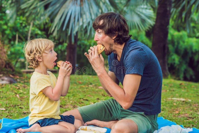 Portret młody ojciec i jego syn cieszy się hamburger w ono uśmiecha się i parku zdjęcie stock