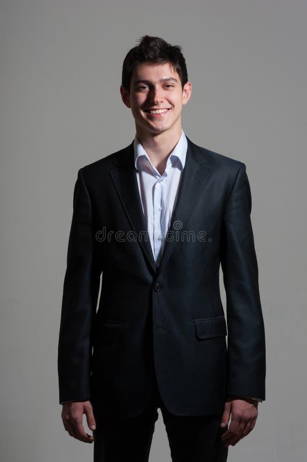 Portret młody ono uśmiecha się przystojny biznesowy mężczyzna w kostiumu na popielatym fotografia stock
