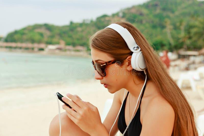 Portret młody piękno nastolatka dziewczyny obsiadanie białą piasek plażą słucha muzyka używać hełmofony i smartphone przeciw dale zdjęcie royalty free
