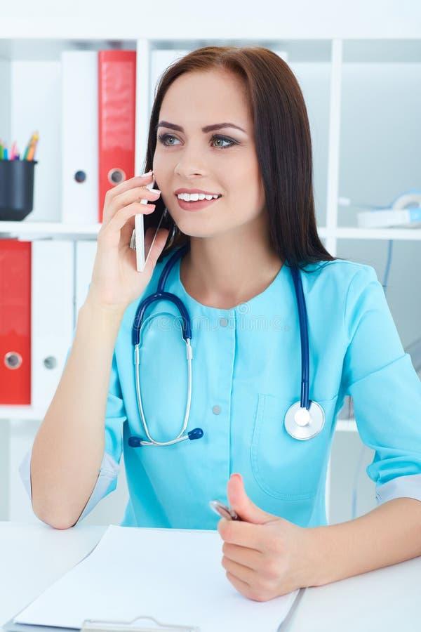 Portret młody piękny żeński lekarz medycyny opowiada na telefonie Medyczny pomocy lub ubezpieczenia pojęcie obraz royalty free