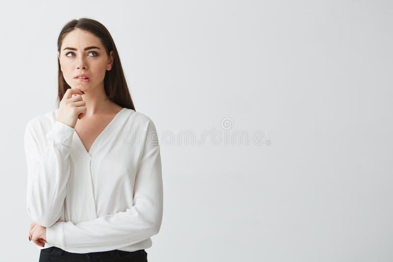 Portret młody piękny brunetka bizneswoman marzy myśleć marszczyć brwi nad białym tłem Ręka na podbródku zdjęcie stock