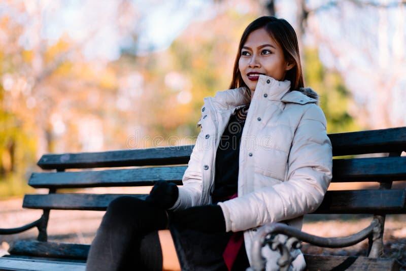 Portret młody piękny kobiety obsiadanie na ławce w eleganckim ciepłym stroju w pogodnym jesień dniu w parku Przypadkowy styl życi obrazy stock