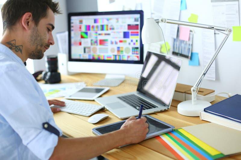 Portret młody projektanta obsiadanie przy graficznym studiiem przed laptopem i komputerem podczas gdy pracujący online obraz stock