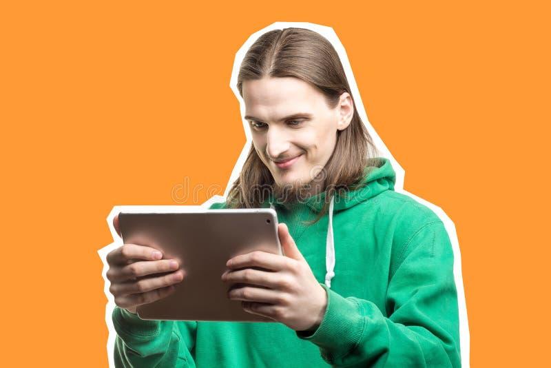 Portret młody przystojny brodaty uśmiechnięty mężczyzna patrzeje cyfrową pastylkę w jego w zielonym hoodie ręki zdjęcie royalty free