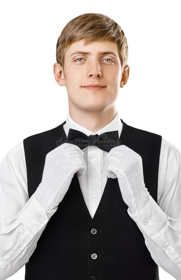 Portret młody przystojny kelner załatwia jego łęku krawat na kostiumu obraz royalty free