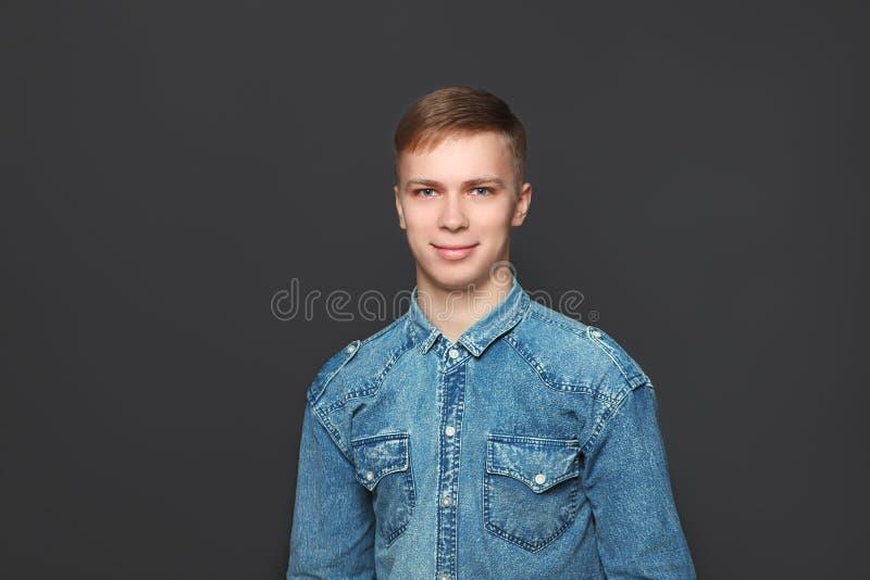Portret młody przystojny mężczyzna w cajgów koszulowej patrzeje kamerze nad zmroku popielatym tłem Emocje i wyrazu twarzy pojęcie obraz stock