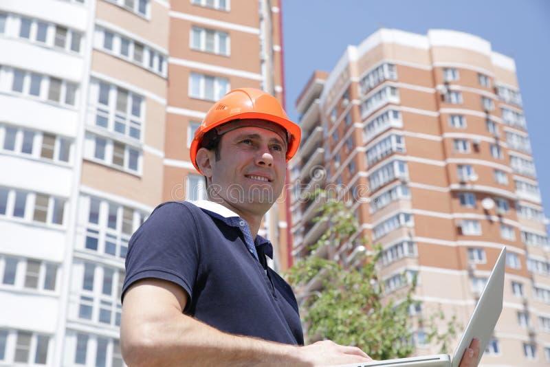 Portret młody przystojny mężczyzna w ochronnym hełmie z laptopem w jego rękach przed wysokim budynkiem zdjęcie royalty free