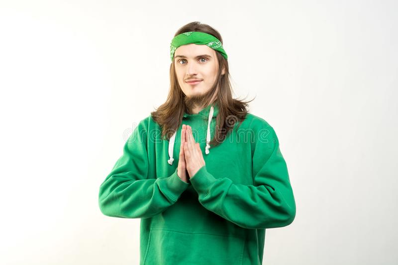 Portret młody przystojny mężczyzna w zielonym hoodie z pokojowym uśmiechem pokazuje namaste agains bielu tło zdjęcia stock