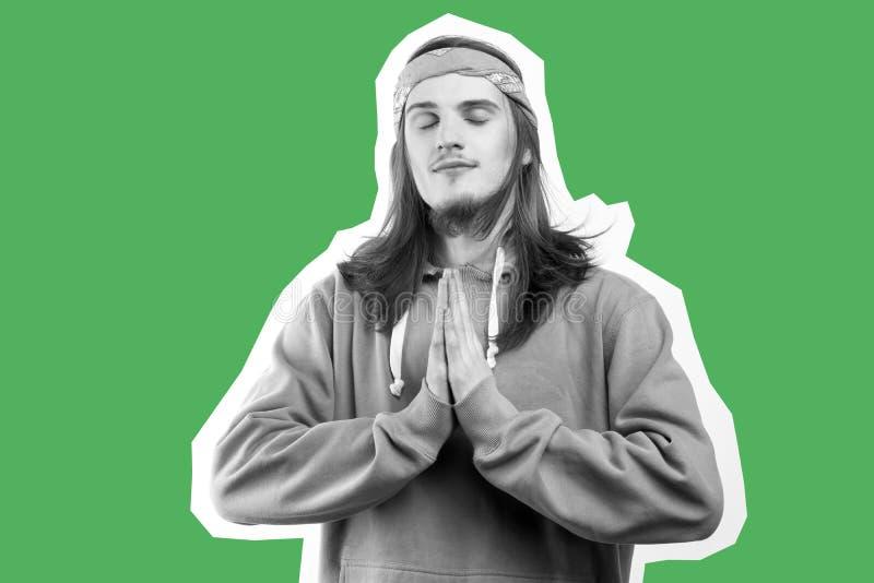Portret młody przystojny mężczyzna w zielonym hoodie zamknięci oczy i pokazywać namaste z pokojowym uśmiechem, zielony tło obrazy stock