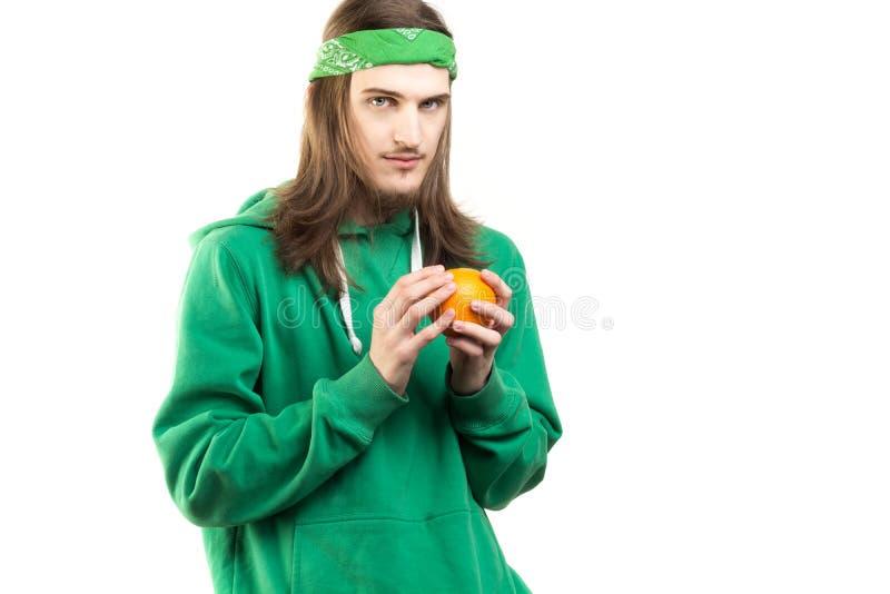 Portret młody przystojny z paciorkami mężczyzna trzyma pomarańcze w jego w zielonym hoodie ręki fotografia royalty free