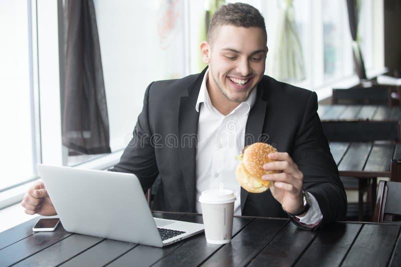 Portret młody rozochocony biznesmena łasowania hamburger podczas gdy wo obrazy stock