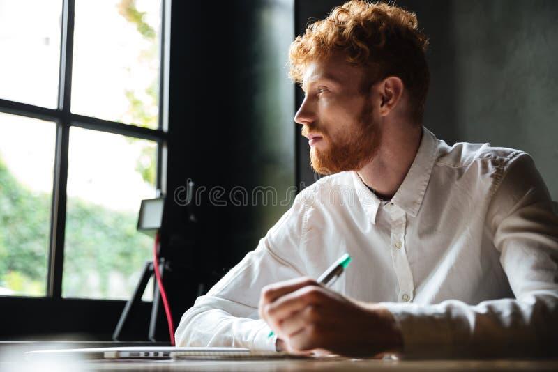 Portret młody rudzielec mężczyzna writing w notatniku fotografia royalty free
