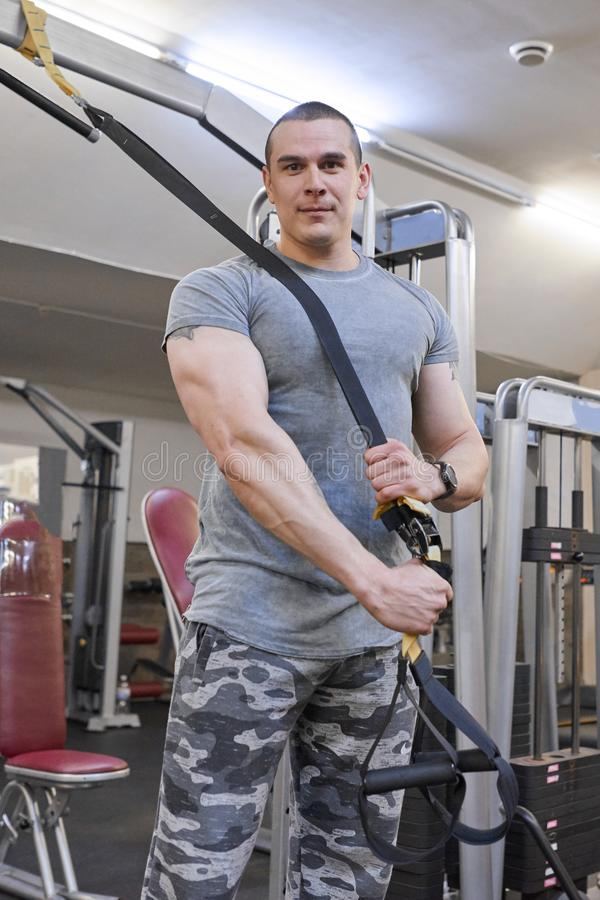 Portret młody silny ono uśmiecha się mięśniowy uśmiechnięty mężczyzna w gym Samiec z sprawności fizycznych patek pętlami obraz stock