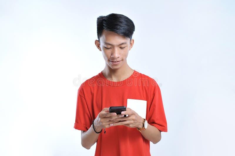 Portret młody studencki azjatykci mężczyzna opowiada na telefonie komórkowym, mówi szczęśliwego uśmiech zdjęcia stock