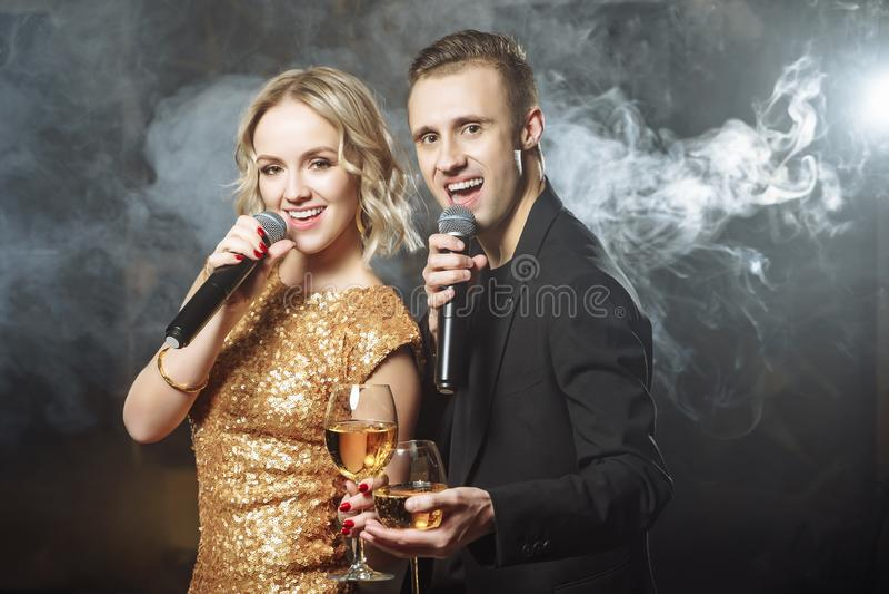 Portret młody szczęśliwy para śpiew w mikrofon w klubie obrazy stock