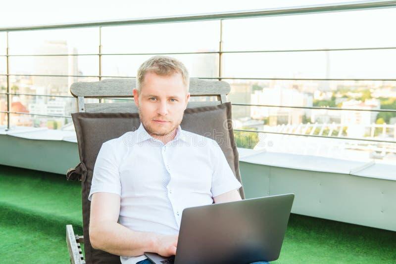 Portret Młody uśmiechnięty biznesmen pracuje na laptopie swobodnie siedzi na deckchair na biuro tarasie z Miastowym krajobrazem d obraz stock