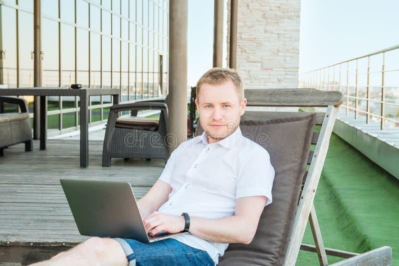 Portret Młody uśmiechnięty biznesmen pracuje na laptopie swobodnie siedzi na deckchair na biuro tarasie z Miastowym krajobrazem d zdjęcia stock