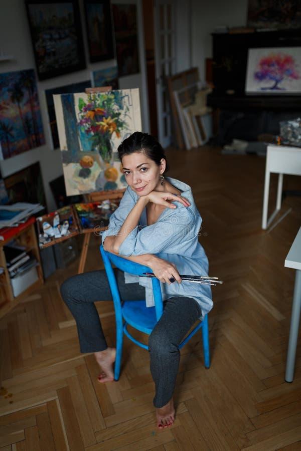 Portret młody uśmiechnięty brunetki kobiety artysta w jej studiu zdjęcia stock