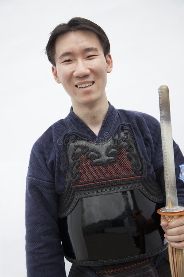 Portret młody uśmiechnięty mężczyzna trzyma kordzika w tradycyjnej Japońskiej odzieży, studio strzał obrazy stock