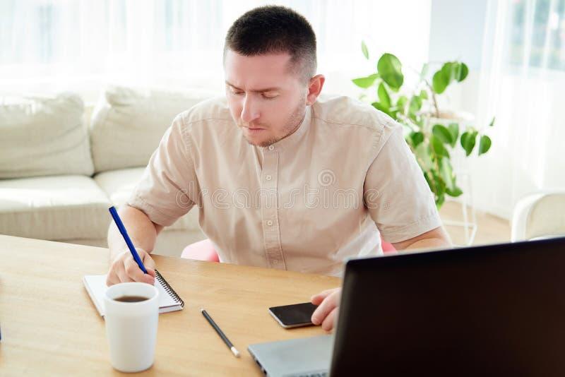 Portret młody ufny kierownik robi notatkom i działaniu na laptopie, kopii przestrzeń Przystojny biznesmena obsiadanie przy drewne obraz stock