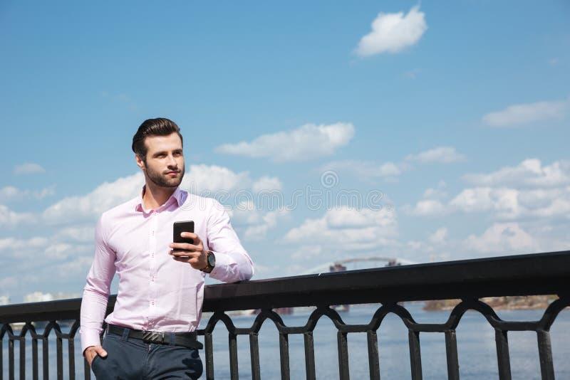 Portret młody ufny mężczyzna używa smartphone blisko rzeki obrazy stock