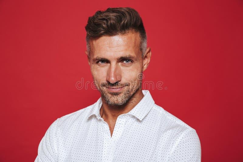 Portret młody zarośnięty mężczyzna 30s w biały koszulowy patrzeć na krzywka fotografia royalty free