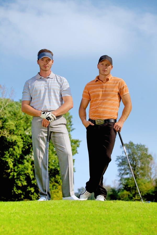 Portret młodzi człowiecy stoi z golfem wtyka na polu golfowym obraz stock