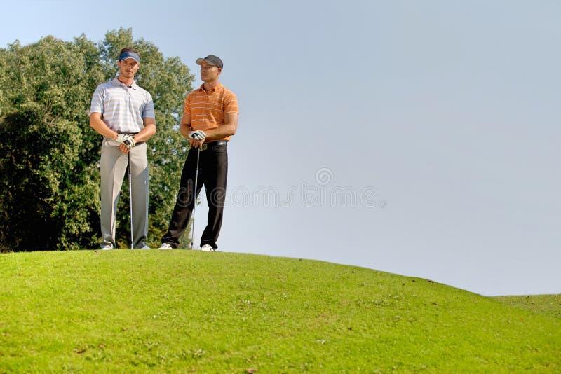 Portret młodzi człowiecy stoi z golfem wtyka na polu golfowym zdjęcie stock