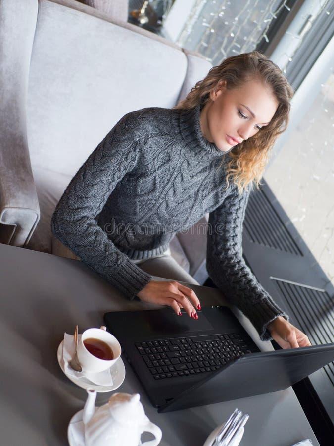 Portret młodzi piękni bizneswomany cieszy się kawę podczas pracy na przenośnym laptopie, powabna kobieta zdjęcie stock