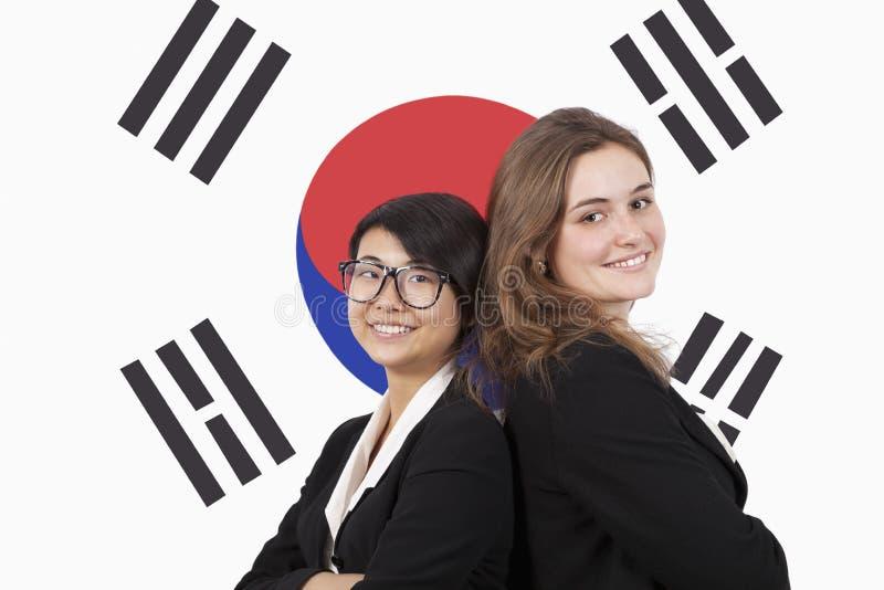 Portret młodzi wieloetniczni bizneswomany ono uśmiecha się nad koreańczyk flaga obraz stock