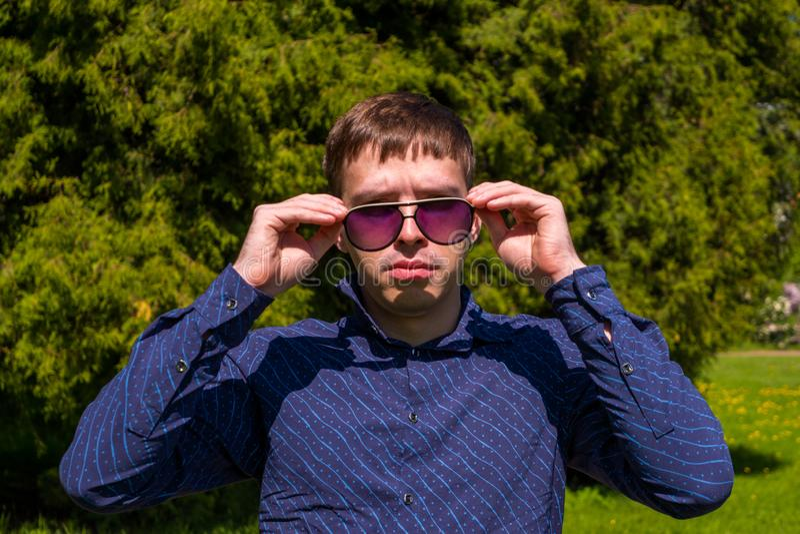 Portret m??czyzna w okularach przeciws?onecznych i b??kitny koszulowy trwanie outside w parku obraz stock