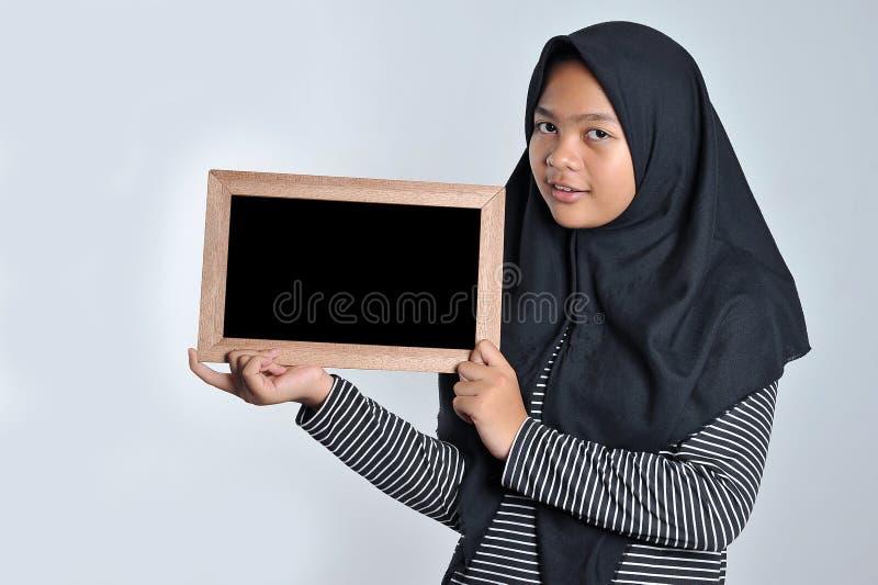 Portret m?oda azjatykcia kobieta w islamskim chustki na g?ow? mienia chalkboard U?miechni?ta azjatykcia kobieta jest ubranym isla obraz royalty free