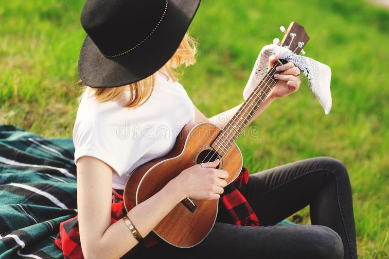 Portret m?oda pi?kna kobieta w czarnym kapeluszu Dziewczyny obsiadanie na bawi? si? gitarze i trawie obraz stock