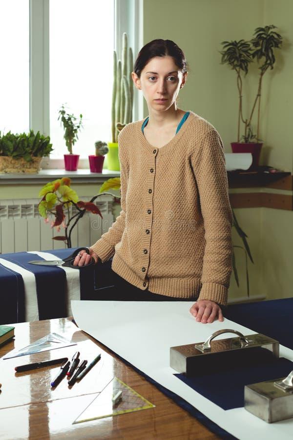 Portret m?odej kobiety szwaczka w domowym studiu Patrzeje appraisingly przy klientem Trzyma? par? no?yce (zestaw) Handmade poj?ci zdjęcie stock
