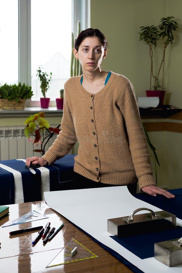 Portret m?odej kobiety szwaczka w domowym studiu Patrzeje appraisingly przy klientem Trzyma? par? no?yce (zestaw) Handmade poj?ci obraz stock