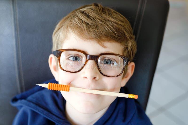 Portret mała śliczna szkolna dzieciak chłopiec z szkłami Piękny szczęśliwy dziecko patrzeje kamerę Uczeń robi zabawie obrazy royalty free