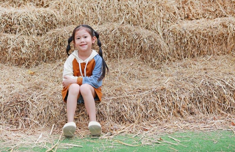 Portret małe dziecko dziewczyna i grże odzieżowego obsiadanie na stosie słoma na zima sezonie zdjęcie royalty free