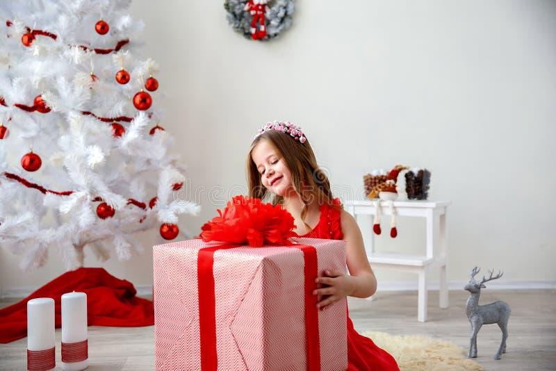 Portret mała śliczna dziewczyna z Bożenarodzeniową teraźniejszością Strzelający z selekcyjną ostrością zdjęcia stock