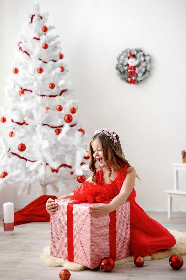 Portret mała śliczna dziewczyna z Bożenarodzeniową teraźniejszością Strzelający z selekcyjną ostrością zdjęcie royalty free