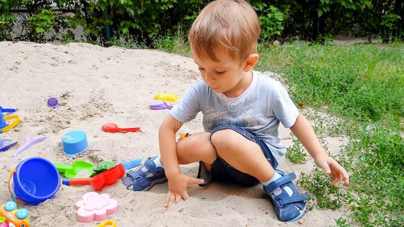 Portret mała berbeć chłopiec bawić się z zabawkami i kopiącym piaskiem w piaskownicie przy parkiem zdjęcie stock