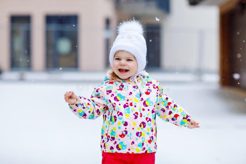 Portret mała berbeć dziewczyna chodzi outdoors w zimie Ślicznego berbecia łasowania lollypop słodki cukierek ma się dziecko obraz royalty free