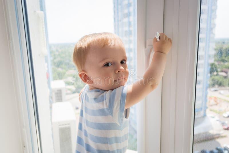 Portret mała dziecko pozycja na nadokiennym parapecie i próbować otwierać okno zdjęcie royalty free