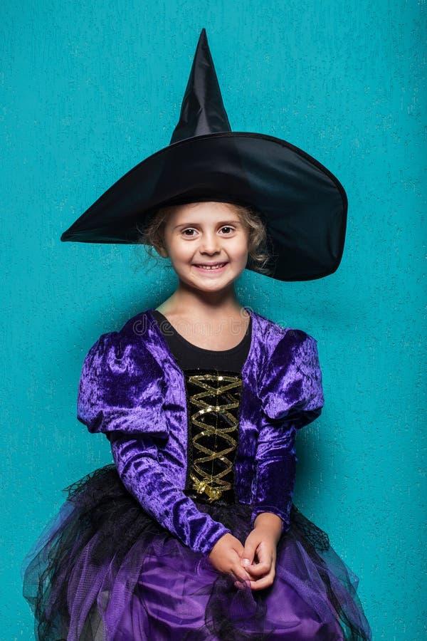 Portret mała dziewczynka w czarnego kapeluszu i czarownicy odzieży halloween czarodziejka bajka Pracowniany portret na błękitnym  obraz stock