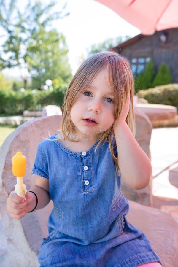 Portret mała dziewczynka z pomarańczowym lodowym lolly w parku zdjęcia royalty free