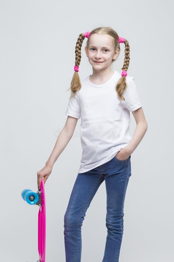 Portret Mała Kaukaska Blond dziewczyna z Ładnymi Pigtails Pozuje Z Różowym Pennyboard zdjęcia stock