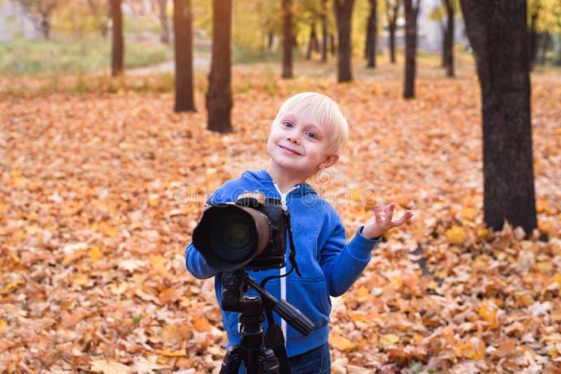Portret małego blondyna z dużą kamerą DSLR na trójnogu. Sesja fotograficzna w jesiennym parku fotografia royalty free
